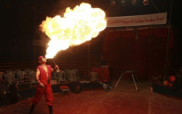 In this photo taken Thursday, Oct. 25, 2012, Rifat al-Gureisy, 55, a member of the Egyptian National Circus, blows fire during a practice in Gaza City. The circus came to Gaza on Friday, accompanied by blaring music, juggling clowns and fire blowers — but getting it there required its own high-wire act. No women performers were included for fear of offending conservative Palestinians and the Gaza Strip's militant Hamas rulers, and the circus' lone lion and tiger were left behind because of the high cost of transporting them legally into Gaza. (AP Photo/Adel Hana)
