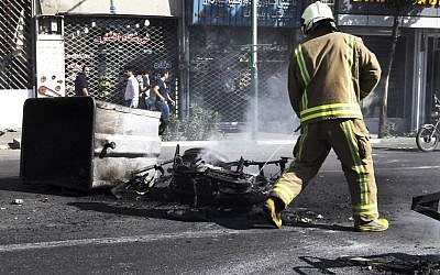 In this photo obtained by the Associated Press, an Iranian fire fighter extinguishes a burned motorcycle in a street in central Tehran, near Tehran's old main bazaar, during currency protests, Wednesday, October 3, 2012.  (photo credit: AP)