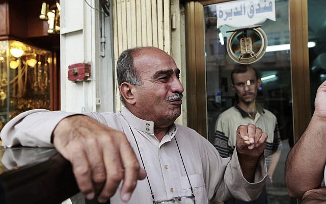 Baghdad moneylender Rasheed al-Sheikh reacts during an interview with the Associated Press after being asked about threats made against Syria's Sayyida Zainab shrine, on October 22, 2012 (photo credit: AP Photo/Hadi Mizban)