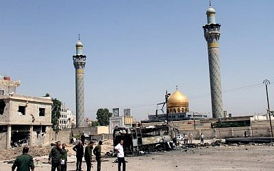 This June 14, 2012 photo shows Syrian security forces at the site where a car bomb exploded near the shrine of Sayyida Zeinab, visible in the background, in a suburb of Damascus, Syria (photo credit:AP Photo/Bassem Tellawi)
