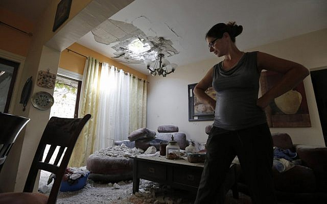 A woman surveys the damage to her house after a rocket fired by Palestinian terrorists from the Gaza Strip hit a community in southern Israel, Wednesday, Oct. 24, 2012 (photo credit: AP/ Tsafrir Abayov)