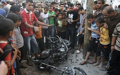 Palestinians gather a round the wreckage of motorcycle following an Israeli air strike in Rafah, southern Gaza Strip, Sunday. Israel said it fired on two Gaza members of an al-Qaida-inspired terror group; one was killed. (photo credit: AP Photo/Eyad Baba)