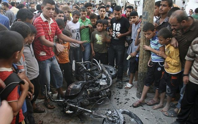 Palestinians gather a round the wreckage of motorcycle following an Israeli air strike in Rafah, southern Gaza Strip, last Sunday. (photo credit: AP Photo/Eyad Baba)