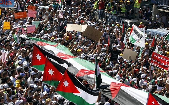 Thousands of Islamic Action Front supporters carrying banners and a large Jordanian flag gather earlier this month to demand constitutional reforms during an opposition rally in Amman. (photo credit: AP/Raad Adayleh)