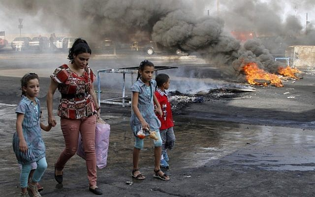 A family walks past flaming tires used as a roadblock to protest the death of Brig. Gen. Wissam al-Hassan, head of the intelligence division of Lebanon's domestic security forces in a car bomb attack targeting his convoy, in the southern port city of Sidon, Lebanon on Saturday. (photo credit: AP Photo/ Mohammed Zaatari)
