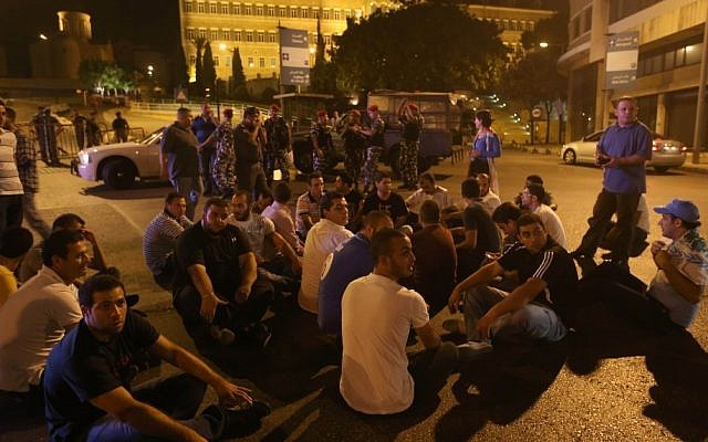 Anti-government protesters in Lebanon sit on the ground Friday in front the government palace, seen in the background, during a demonstration after a bomb killed Brig. Gen. Wissam al-Hassan and seven others in Beirut. (photo credit: AP Photo/Hussein Malla)