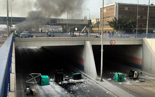 A highway link to Beirut International airport is blocked by garbage containers overturned and set aflame on Saturday by Sunni protesters angry at the killing of Brig. Gen. Wissam al-Hassan last year. (photo credit: AP/Ahmad Omar)