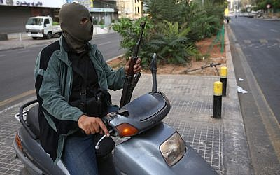 A Sunni gunman holds his AK-47 as he rides a scooter on a blocked street leading to a Shiite neighborhood after overnight clashes between Sunni and Shiite gunmen in Beirut, Lebanon, Monday October 22, 2012 (photo credit: AP/Hussein Malla)