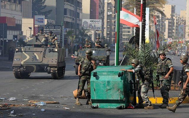 Lebanese Army soldiers remove garbage containers used as a roadblock after overnight clashes between Sunni and Shiite gunmen in Beirut, Lebanon, on Monday, October 22, 2012 (photo credit: AP Photo/Ahmad Omar)