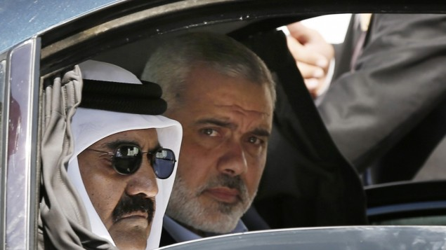 Qatari Emir Sheikh Hamad bin Khalifa al-Thani, left, and Gaza's Hamas prime minister Ismail Haniyeh, right, arrive for a cornerstone laying ceremony for Hamad, a new residential neighborhood in Khan Younis, southern Gaza Strip, October 23 (photo credit: AP/Mohammed Salem)