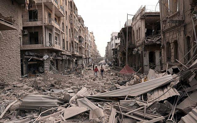 Syrian men walk down a street between destroyed buildings in Syria (photo credit: AP/SANA)