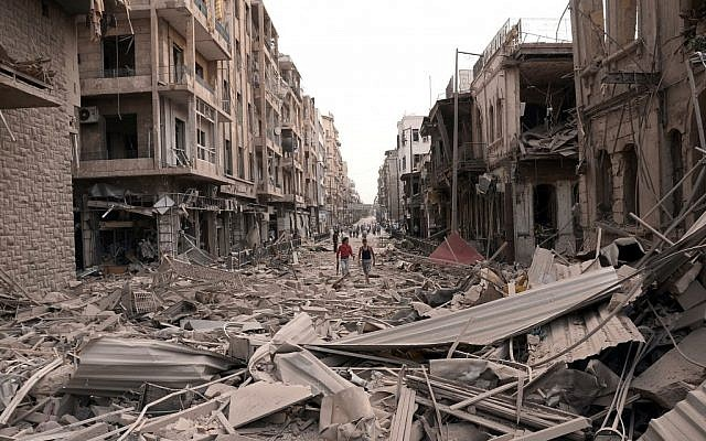 Men walk along a street between destroyed buildings where bombs rocked the Saadallah al-Jabri Square in Aleppo, Syria, on Wednesday, Oct. 3, 2012. (photo credit: SANA/AP)