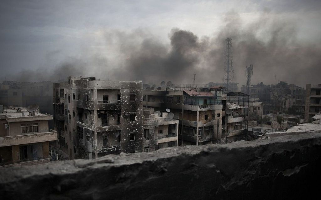 Smoke rises over Saif Al Dawla district in Aleppo, Syria earlier this month (photo credit: AP/ Manu Brabo)
