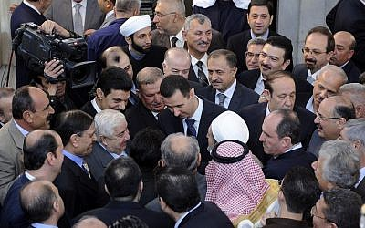 Syrian President Bashar Assad, center, shakes hands with worshipers at a mosque last October. (photo credit: AP)