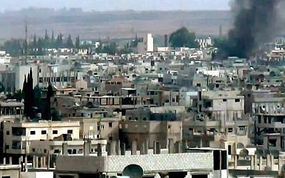 This image taken from video obtained from the Shaam News Network, which has been authenticated based on its contents and other AP reporting, purports to show smoke rising from buildings due to government forces shelling in Daraa, Syria, on Tuesday, Oct. 2, 2012. (photo credit: AP Photo/Shaam News Network via AP video)