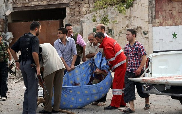 Men carry the body of a casualty in an attack against a government compound in Aleppo Wednesday (photo credit: AP Photo/SANA)