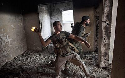 Free Syrian Army soldier throws a petrol bomb at Syrian Army positions in Saif Al Dawle district in Aleppo, October 3 (photo credit: AP/ Manu Brabo)