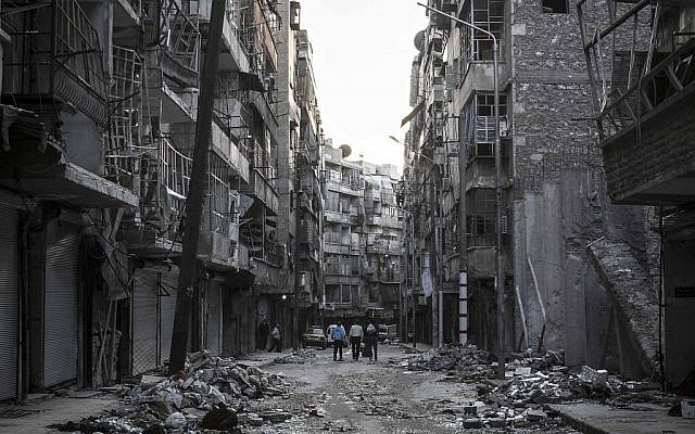 Syrian residents walk on a street among the debris of buildings damaged by heavy shelling in the southeast of Aleppo City, on October 27, 2012 (photo credit: AP Photo/Narciso Contreras)