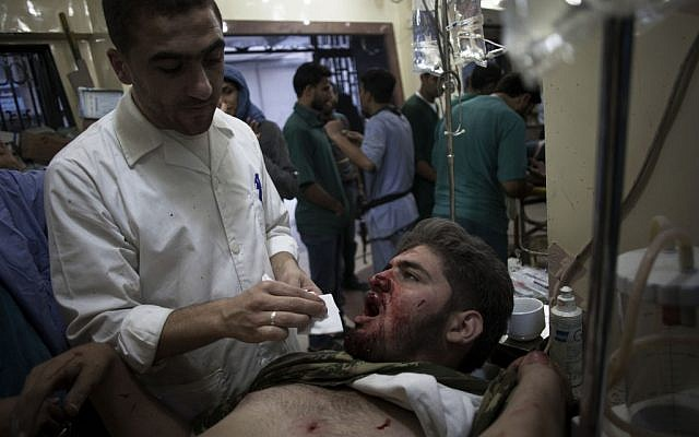 A Syrian doctor treats a wounded Free Syrian Army fighter at Dar al-Shifa hospital in Aleppo, October 13 (AP Photo/ Manu Brabo)