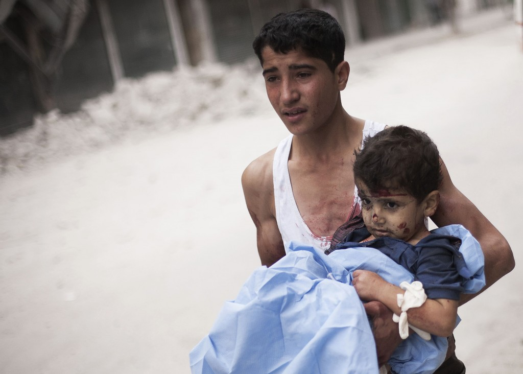 In this Thursday, Oct. 11, 2012 photo, a Syrian youth holds a child wounded by Syrian Army shelling near Dar al-Shifa hospital in Aleppo, Syria (AP Photo/ Manu Brabo)