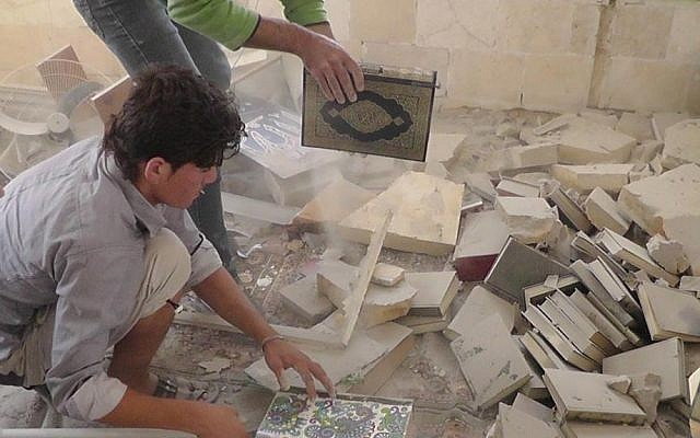 Syrian citizens remove copies of the Quran from under the rubble of a mosque destroyed by government shelling in Idlib province, northern Syria (photo credit: AP/Idlib News Network ENN)