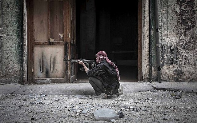 A Free Syrian Army fighter takes aim at a government position in Aleppo, Syria on Wednesday (photo credit: AP/Narciso Contreras)