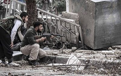Syrian rebel fighters take cover as a Syrian army sniper fires from a destroyed mosque in Tarik Al-Bab, southeast of Aleppo, Syria on Friday, October 26. (photo credit: AP/Narciso Contreras)