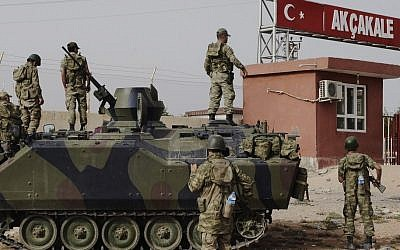 Turkish soldiers patrol a military station at the border crossing with Syria in Akçakale, across from the Syrian rebel-controlled town of Tel Abyad in October. Syria and Turkey exchange fire across their troubled border for a sixth straight day, attacks that look increasingly like an intentional escalation by President Bashar Assad to send a message to his northern neighbor that it will pay dearly for supporting the rebels. (photo credit: AP)