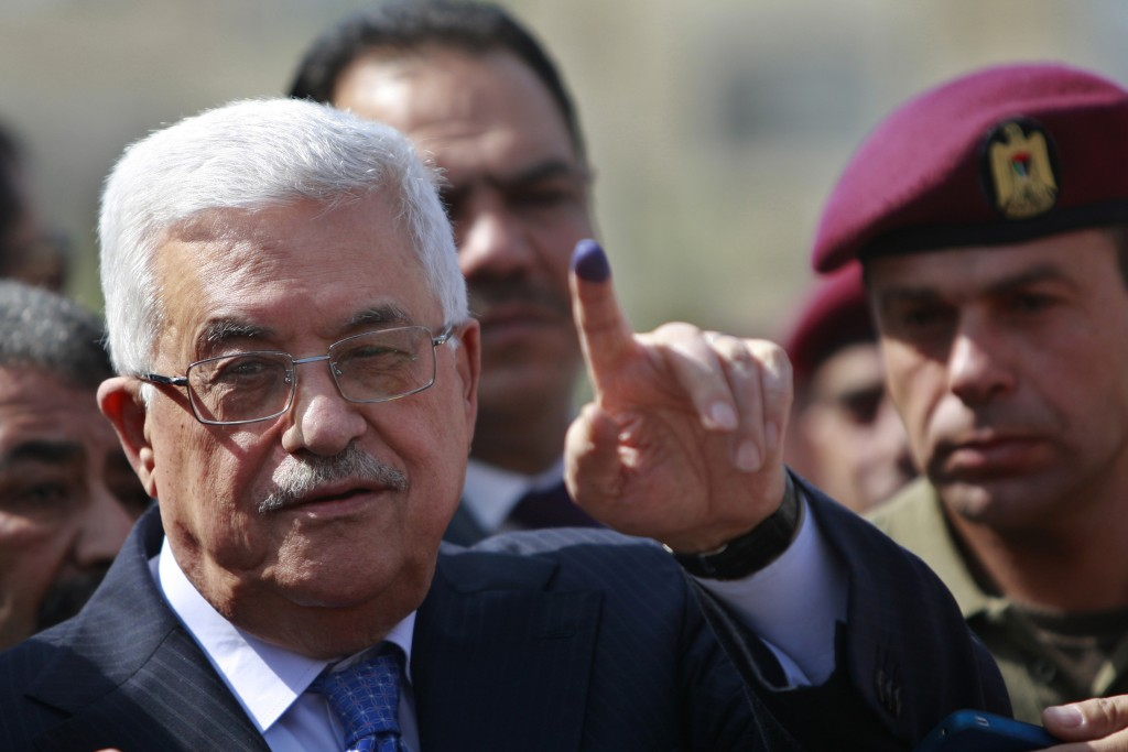 Palestinian President Mahmoud Abbas shows his ink-stained finger after casting his vote during local elections at a polling station in the West Bank city of Ramallah, October 20, 2012. (photo credit: AP/Majdi Mohammed)