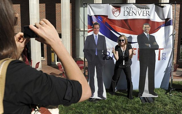 Ellen Leslie, left, takes a photo of Danielle Gillespie, right, with cardboard cut-outs of Mitt Romney and President Barack Obama at DebateFest at the University of Denver on Wednesday, Oct. 3, 2012, in Denver. (Chris Schneider/AP)