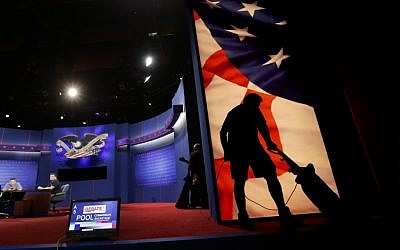 A worker vacuums the set for Monday's presidential debate in Boca Raton, Florida. (photo credit: AP Photo/Eric Gay)