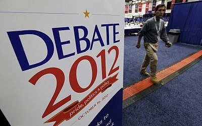 A worker walks past a sign in the media filing center before Tuesday's presidential debate between President Barack Obama and Republican presidential candidate, former Massachusetts Gov. Mitt Romney, Monday, Oct. 15, 2012, at Hofstra University in Hempstead, NY. (photo credit: Charlie Neibergall/AP)