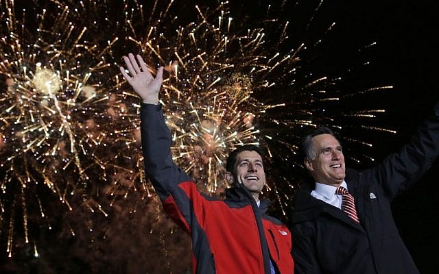 Republican presidential candidate Mitt Romney, right, and his vice presidential running mate, Rep. Paul Ryan, wave as fireworks go off at a campaign event in North Canton, Ohio on Friday (photo credit: AP/Charles Dharapak)