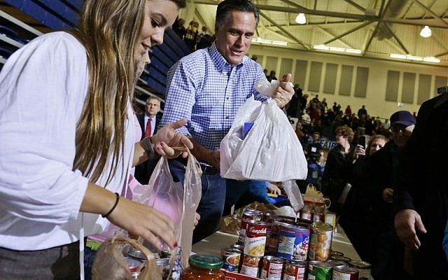 Republican presidential candidate, former Massachusetts Gov. Mitt Romney holds bags of food as he participates in a campaign event collecting supplies from residents local relief organizations for victims of superstorm Sandy, Tuesday, Oct. 30, 2012, at the James S. Trent Arena in Kettering, Ohio. (photo credit: Charles Dharapak/AP)