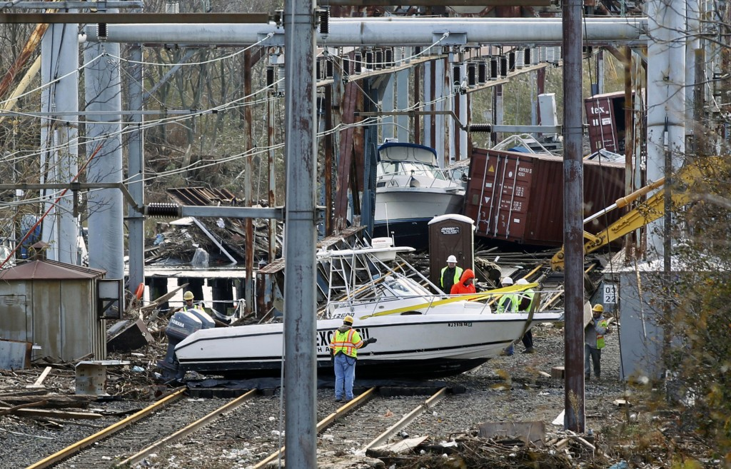 Workers try to clear boats and debris from the New Jersey Transit's Morgan draw bridge Wednesday, Oct. 31(photo credit: Mel Evans/ AP)