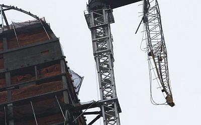 A construction crane atop a luxury high-rise dangles precariously over the streets after collapsing in high winds from Hurricane Sandy, Monday, Oct. 29, 2012, in New York. (photo credit: John Minchillo/AP)