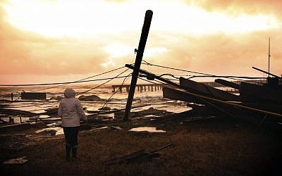 Kim Johnson looks over the destruction near her seaside apartment in Atlantic City, NJ, on Tuesday, October 30. (photo credit: AP/Seth Wenig)