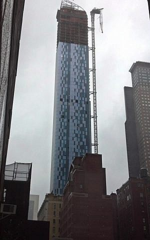A construction crane atop a $1.5 billion luxury high-rise in midtown Manhattan dangles precariously after collapsing in high winds Monday, October 29, as a huge storm bore down on the city. (photo credit: AP/Verena Dobnik)