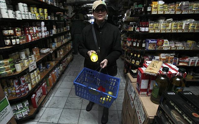 A woman shops for groceries by flashlight in the Tribeca neighborhood of New York, Tuesday, Oct. 30, 2012. (photo credit: Richard Drew/AP)