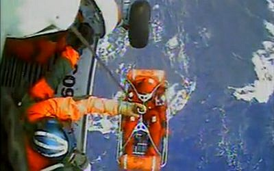 In this video image capture released by the US Coast Guard, a USCG crew member uses a hoist to bring up a survivor from the HMS Bounty into a helicopter. (photo credit: AP/U.S. Coast Guard)