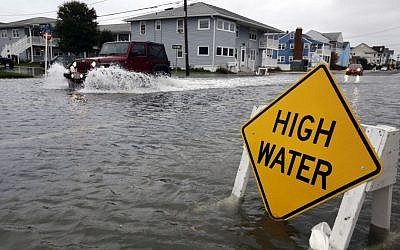A car goes through high water in Ocean City, Maryland, as Hurricane Sandy bears down on the East Coast on Sunday (photo credit: AP/Alex Brandon)