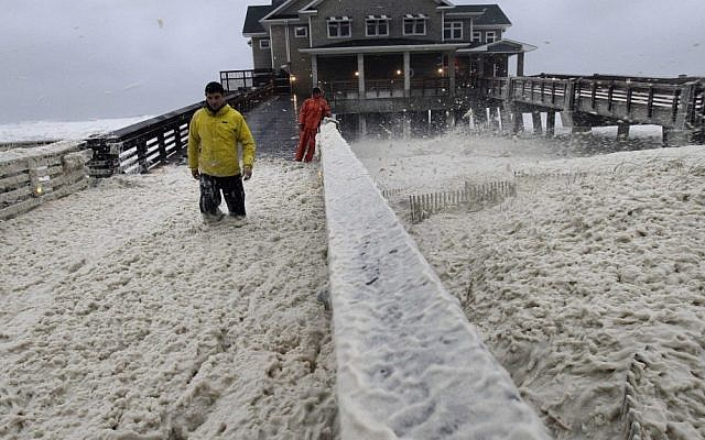 A news crew wades through sea foam in Nags Head, North Carolina, on Sunday, as wind and rain from Hurricane Sandy move into the area. (photo credit: AP/Gerry Broome)