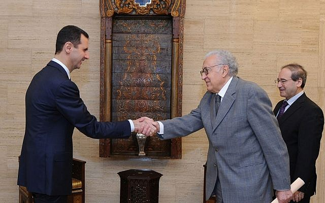 Syrian President Bashar Assad, left, greets UN and Arab League envoy Lakhdar Brahimi prior to their closed-door meeting in Damascus, Syria, Sunday Oct. 21 (photo credit: AP/SANA)