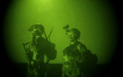 In this Oct. 28, 2008 file photo, taken with a night vision scope, US Special Operations forces are seen during a joint operation with Afghan National Army soldiers targeting insurgents operating in Afghanistan's Farah province. Small teams of US special operations forces arrived at American embassies throughout North Africa to set up a new counterterrorist network months before militants killed the US ambassador in Libya. But officials say the network was too new to stop the Benghazi attack. (photo credit: AP Photo/Maya Alleruzzo)