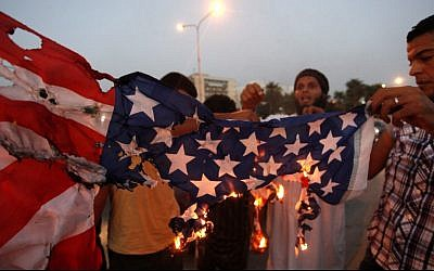 In this Sept. 14, 2012 photo, Libyan followers of Ansar al-Shariah Brigades burn the US flag during a protest in front of the Tibesti Hotel, in Benghazi, Libya. (photo credit: AP Photo / Mohammad Hannon)