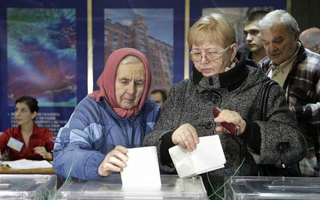 Ukrainians cast their ballots at a polling station in Kiev on Sunday (photo credit: AP/Efrem Lukatsky)