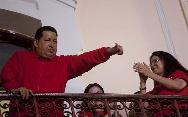 Venezuela's President Hugo Chavez greets his supporters from the Miraflores presidential palace balcony in Caracas, Venezuela, Sunday, Oct. 7, 2012. Chavez won re-election and a new endorsement of his socialist project Sunday, surviving his closest race yet after a bitter campaign against opposition candidate Henrique Capriles.(photo credit: AP Photo/Rodrigo Abd)