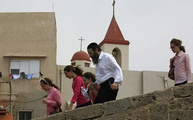 A religious Jewish family walks past a church in Acre's Old City (photo credit: Nati Shohat/Flash90)