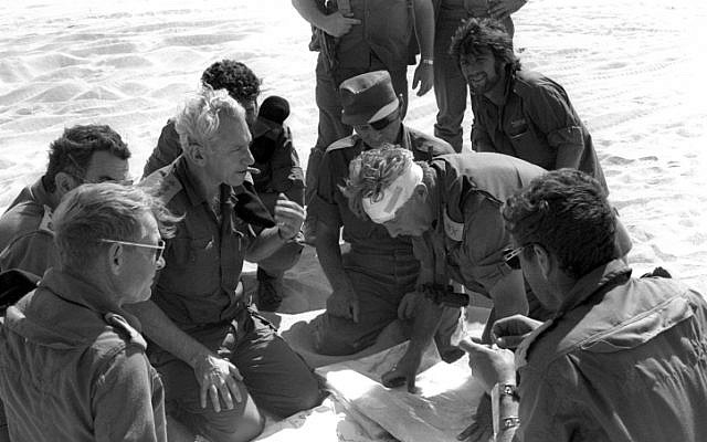 Divisional commander Ariel Sharon consulting with Lt. Gen. Chaim Bar-Lev and other officers on the southern front (Photo credit: GPO/ Flash 90)