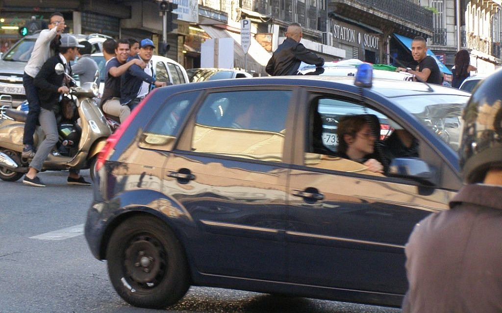 Young Arab residents of Marseille taunt police as they drive recklessly down a central avenue last month. (Cnaan Liphshiz/JTA)